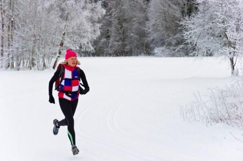 Women jogging through snowy forest.